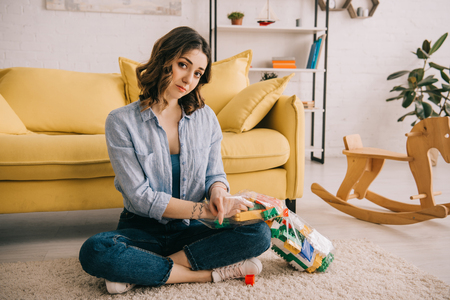 tired woman with toy blocks sitting on carpet with crossed legs