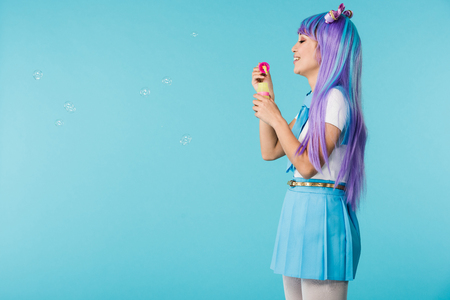 Side view of anime girl with soap bubbles isolated on blue