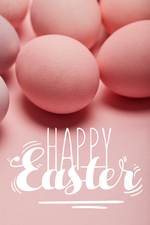 painted pink eggs on pink surface with happy Easter lettering Imagens