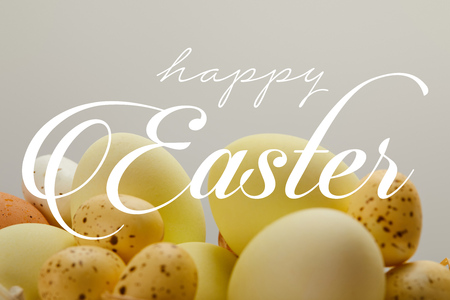 yellow painted chicken and quail eggs with happy Easter lettering on grey background Фото со стока