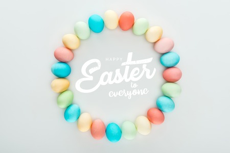 top view of round frame made of painted multicolored eggs with happy Easter to everyone white lettering