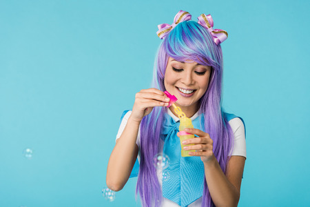 Asian anime girl in purple wig with soap bubbles isolated on blue Stock Photo