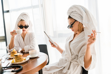 stylish women in bathrobes, sunglasses and jewelry with towels on heads smoking cigarette and reading newspaper at morning