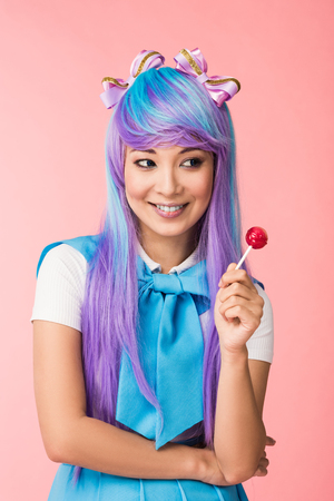 Dreamy asian anime girl in wig holding lollipop isolated on pink Stock Photo