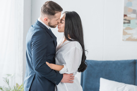 happy bearded man in suit kissing nose of attractive girlfriend in white shirt