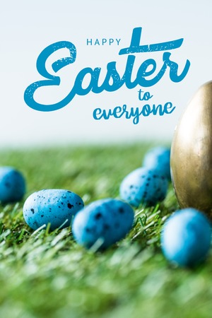 blue painted quail eggs on green grass near golden chicken egg and happy Easter to everyone lettering