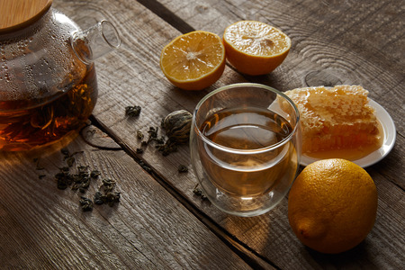 lemons, honeycomb and transparent teapot with glass of traditional chinese blooming tea on wooden table