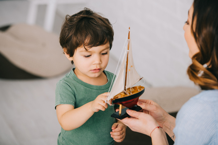 Cropped view of mother and little son with toy ship