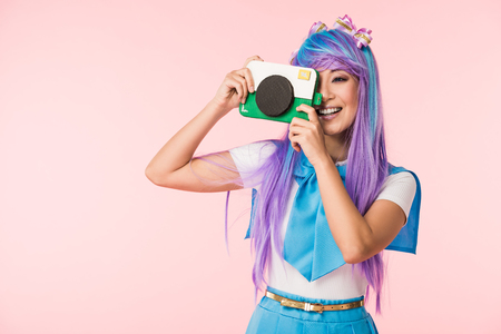 Smiling asian anime girl in purple wig holding cardboard camera isolated on pink Stock Photo