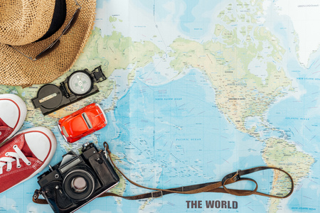 Top view of gumshoes, straw hat, film camera, sunglasses. toy car and compass on world map