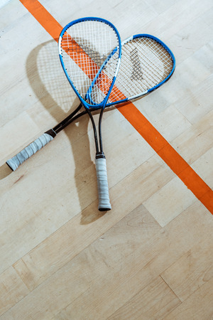 Two squash rackets on wooden floor in four-walled court