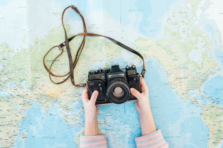 Cropped view of child holding film camera on world map Stockfoto
