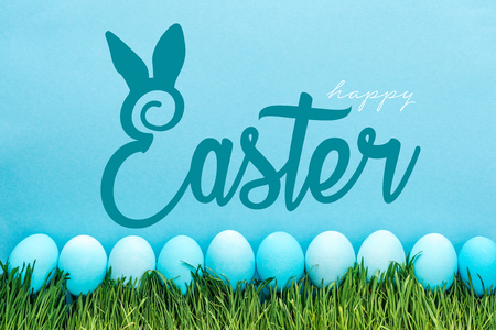 blue painted chicken eggs on green grass with happy Easter lettering on blue background