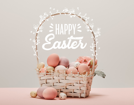 wicker basket with pink painted eggs, flowers and happy Easter lettering on grey background Фото со стока