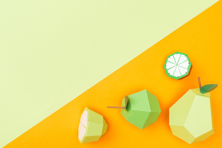 top view of handmade colorful origami fruits on orange and green with copy space