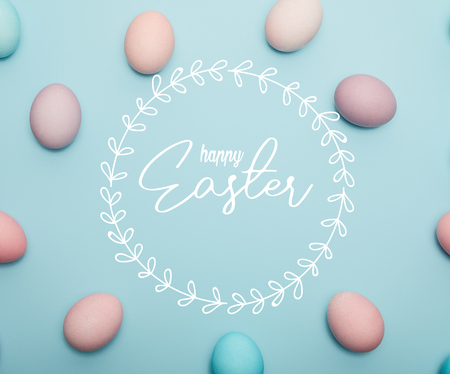 top view of painted multicolored eggs on blue background with happy Easter lettering