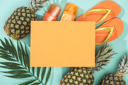 top view of pineapples, tropical leaf, sunscreens, orange flip flops and empty card on turquoise background
