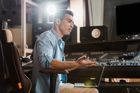 handsome concentrated mixed race sound producer working in recording studio at mixing console Stok Fotoğraf