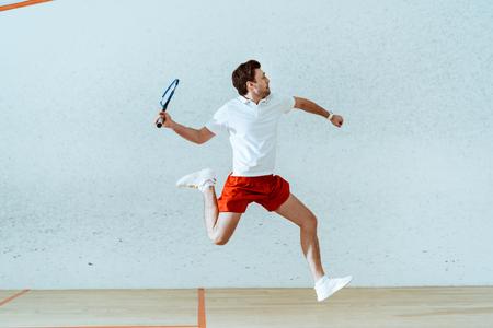 Sportivo in polo che salta mentre gioca a squash in un campo a quattro pareti Archivio Fotografico