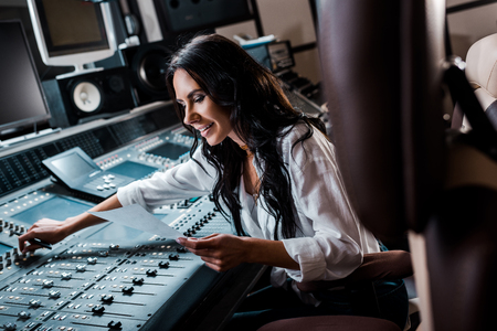 attractive smiling sound producer working at mixing console in recording studio