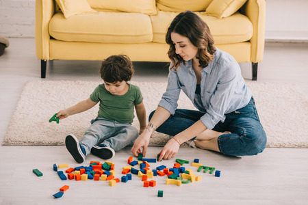 Mother and son playing with toy blocks on carpet 스톡 콘텐츠 - 121461971