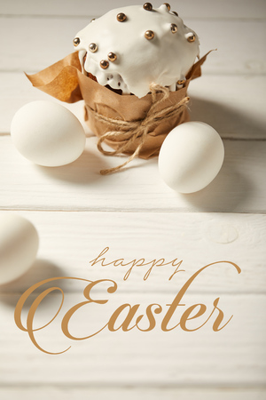 Traditional Easter cake and chicken eggs on white wooden table with happy Easter lettering