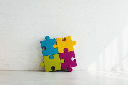 Colorful connected jigsaw pieces near white brick wall at home