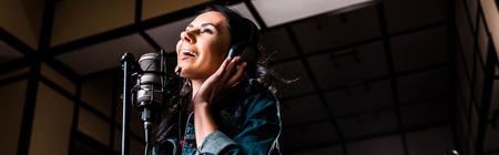 Panoramic shot of beautiful inspired woman singing near microphone in recording studio Reklamní fotografie - 121432081