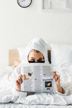 woman in sunglasses, jewelry and with towel on head reading business newspaper in bed Banco de Imagens - 121432047