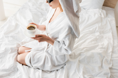 cropped view of stylish woman in bathrobe and sunglasses, towel and jewelry drinking coffee in bed