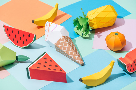 Origami ice cream and handmade cardboard fruits on multicolored paper background