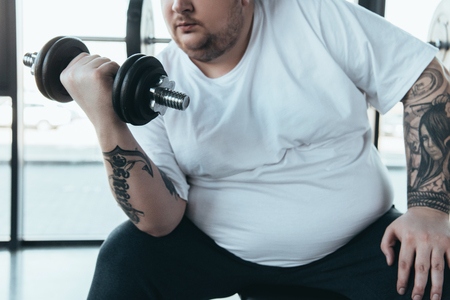 partial view of Overweight tattooed man in white t-shirt training with dumbbell at gym Stock Photo
