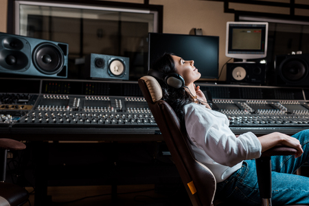 pretty sound producer listening music in headphones while sitting in office chair in recording studio