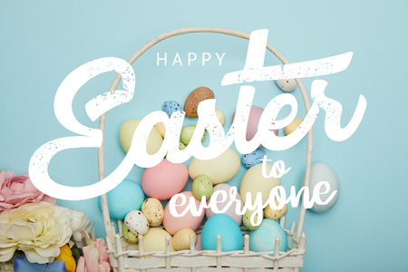 top view of painted multicolored eggs, wicker basket and flowers on blue background with happy Easter to everyone lettering Фото со стока