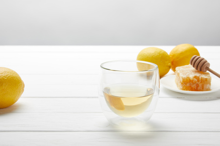 transparent glass with green tea, lemons and honeycomb on white wooden table