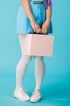 Cropped view of girl in skirt holding briefcase on blue 写真素材