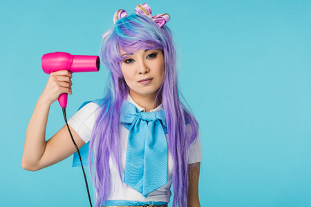 Front view of serious asian anime girl in wig holding hairdryer isolated on blue