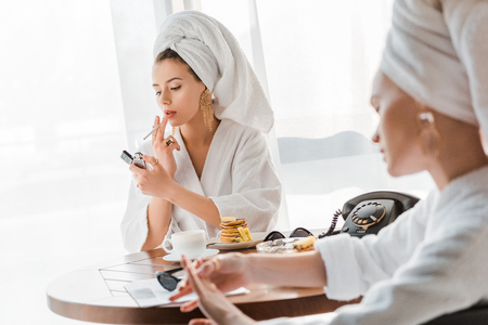 selective focus of stylish woman in bathrobe and jewelry with towel on head lighting up cigarette while friend looking at hand