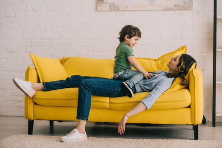 little boy sitting on tired mother while she lying on yellow sofa in living room Banco de Imagens