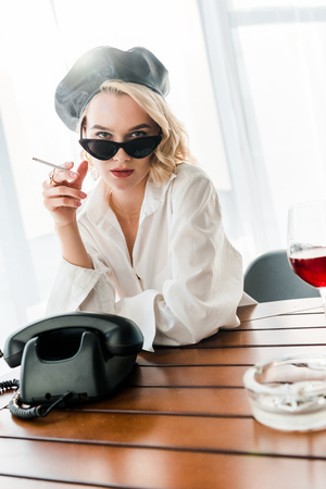 elegant blonde woman in black beret and sunglasses smoking cigarette while sitting near retro phone and glass of red wine Stock Photo