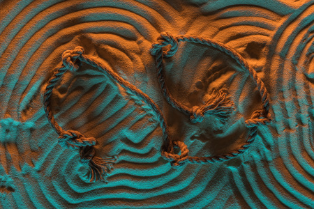 top view of arc lines traces of rope and ropes with knots on sand with orange and blue lights