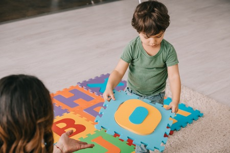 cropped view of mother and son learning alphabet with puzzle mat Stock Photo