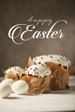 traditional decorated Easter bread and white chicken eggs on white table with happy easter lettering Stock Photo