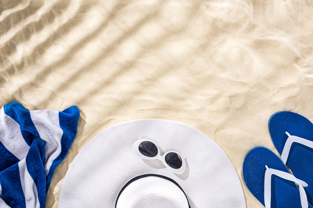 top view of striped towel, retro sunglasses, floppy hat and blue flip flops on sand with shadows and copy space