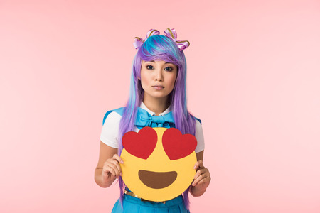Anime girl in purple wig holding infatuation emoticon isolated on pink Banco de Imagens