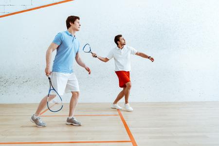Vista de longitud completa de dos deportistas jugando squash en cancha de cuatro paredes