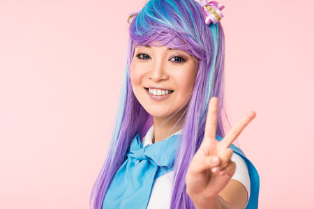 Blissful asian anime girl in purple wig showing peace sign isolated on pink 스톡 콘텐츠