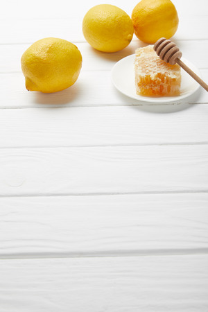 honeycomb and honey dripper on plate with lemons on white wooden table with copy space Reklamní fotografie