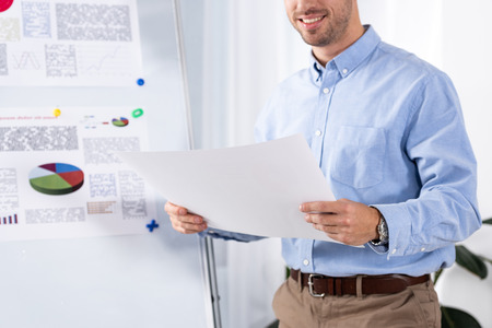 cropped view of cheerful businessman holding blank paper in office
