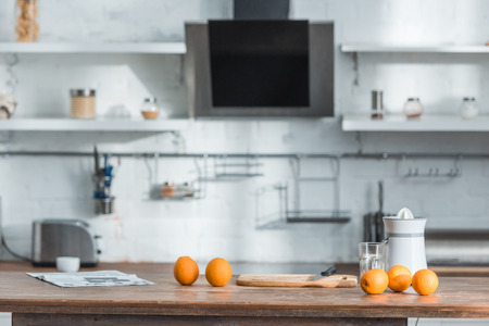 Modern kitchen with juicer, glass and tasty organic oranges on wooden table Stockfoto